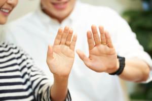 夫婦が指輪のついたお互いの手を見て微笑んでいる