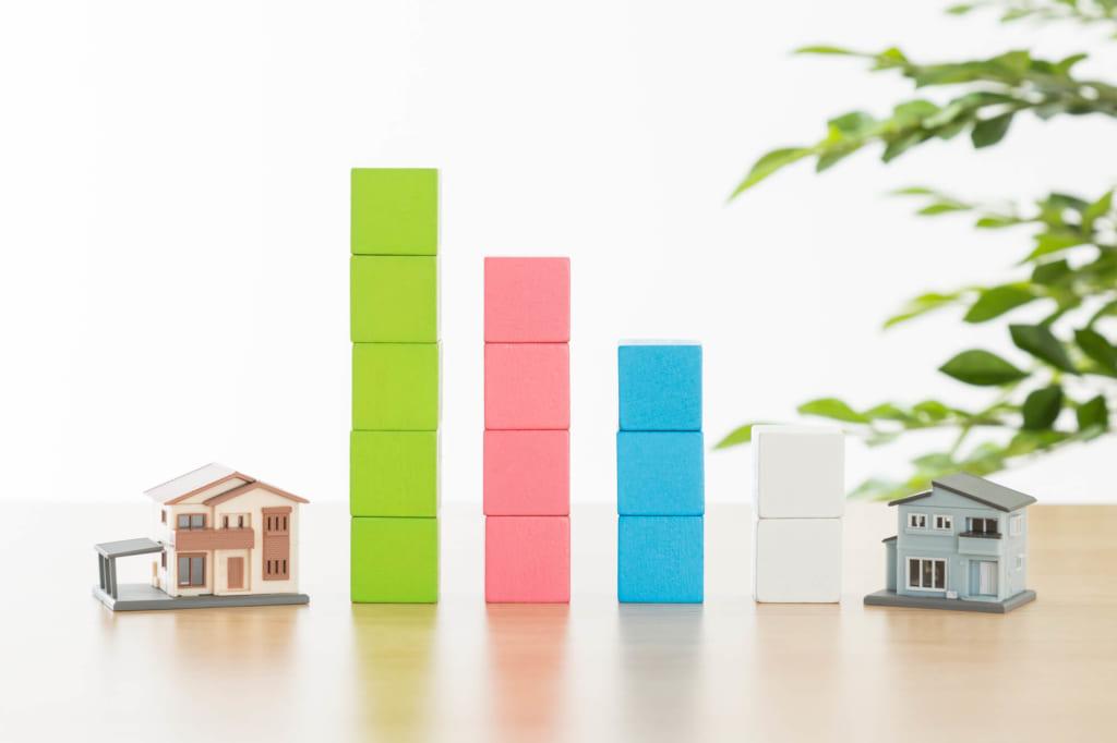 一軒家の模型と、グラフを模して重ね並んだ積木
